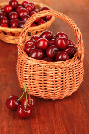 Cherry berries in wicker baskets on wooden table close-up photo