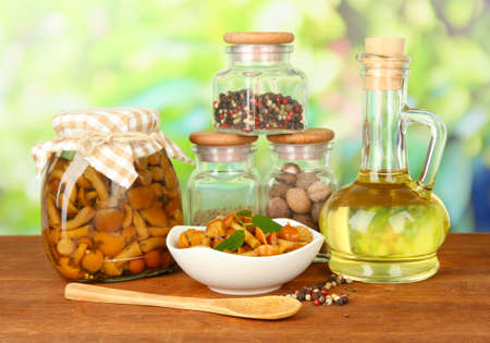 three shelves: Composition of delicious marinated mushrooms, oil and spices on wooden table on bright background