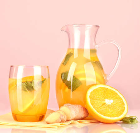 Orange lemonade in pitcher and glass on pink background photo