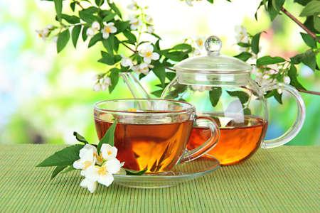 ジャスミン、竹マット、明るい背景とお茶のカップ