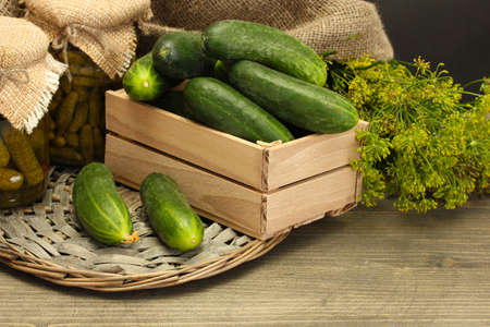 fresh cucumbers in wooden box, pickles and dill, on grey wooden background photo