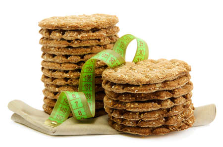 tasty crispbread and measuring tape, isolated on white photo