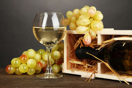 dura: Wooden case with wine bottle, wineglass and grape on wooden table on grey background