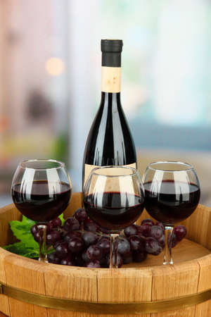 Composition of wine bottle, glasses and  grape, on wooden tray, on bright background photo