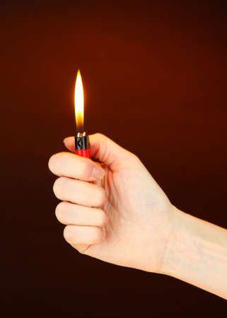 Burning lighter in female hand, on dark brown background photo