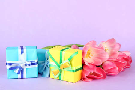 Pink tulips and gift boxes, on color background photo