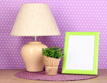 table lamp: Colorful photo frame, lamp and flowers on wooden table on lilac polka dots background Stock Photo