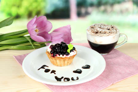 Sweet cake with blackberry and chocolate sauce on plate, with coffee, on bright background photo