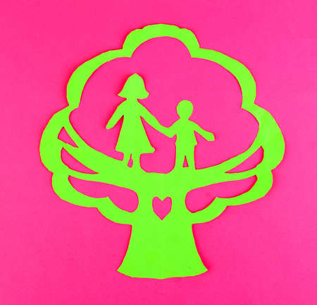 Green cut out paper tree with people inside, on color background photo
