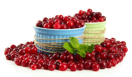 Ripe red cranberries in bowls, isolated on white  photo