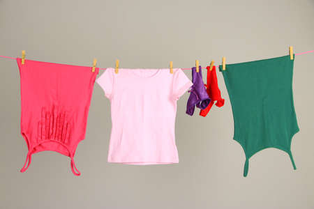 Laundry line with clothes on wall background photo