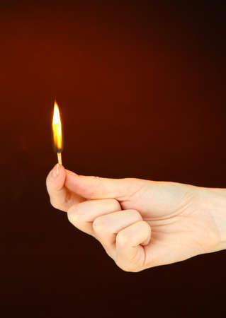 Burning match in female hand, on dark brown background photo