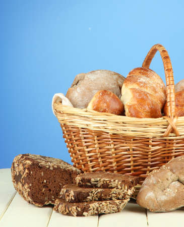 Composition with bread and rolls, in wicker basket on wooden table, on color background photo