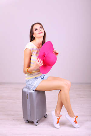 Beautiful girl with suitcase in room photo