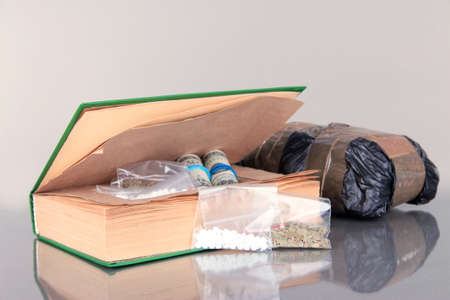 narcotics: Narcotics in book-hiding place and packages on gray background Stock Photo