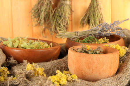 bagging: Medicinal Herbs in wooden bowls on bagging on table on wooden background Stock Photo