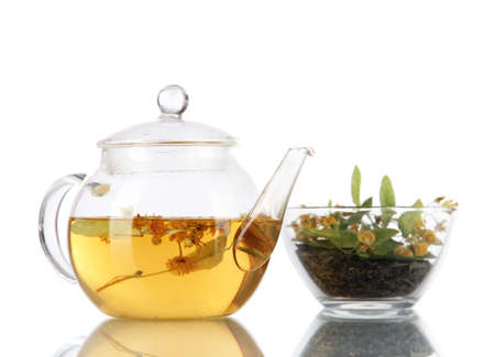 medicinal: Kettle and bowl of tea with linden on  wooden table nature background