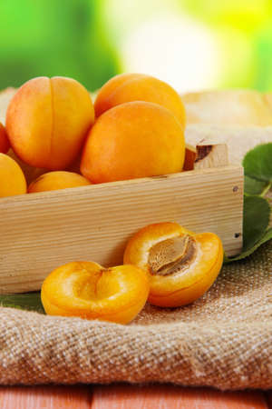 bagging: Apricots in drawer on bagging on wooden table on nature background Stock Photo