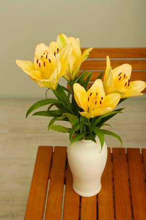 Beautiful orange lilies in vase on wooden table Stock Photo - 20968178