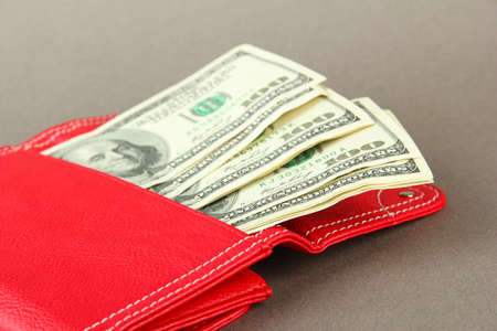 Purse with hundred dollar banknotes, on color background photo