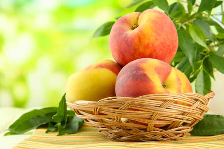 Ripe sweet peaches in basket on table, outdoors Stock Photo