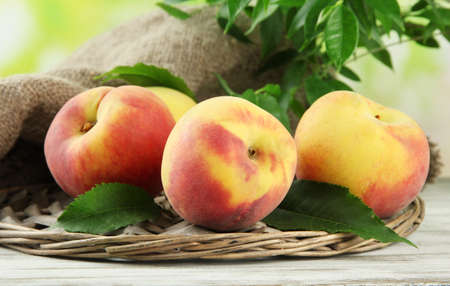 velvety: Ripe sweet peaches on wooden table in garden, close up