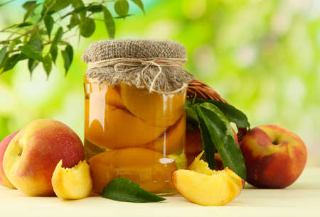 Jar of canned peaches and fresh peaches on wooden table, outside photo