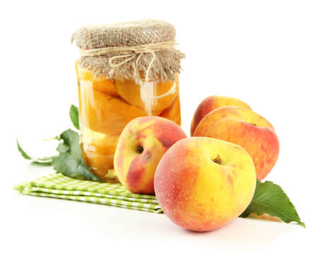 Jar of canned peaches and fresh peaches, isolated on white photo