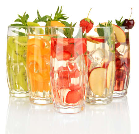 Glasses of fruit drinks with ice cubes isolated on white photo