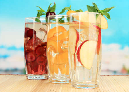 Glasses of fruit drinks with ice cubes on blue background photo