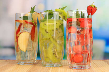 Glasses of fruit drinks with ice cubes on table in cafe photo