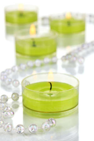 votive: Lighted candles with beads close up