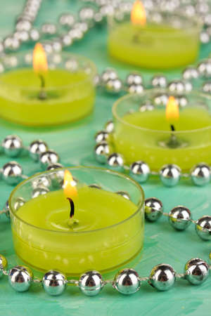 Lighted candles with beads on green background photo