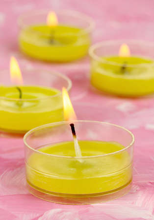 Lighted candles with beads on pink background photo