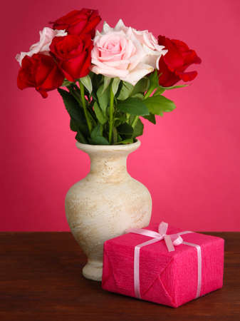 Beautiful bouquet of roses in vase with gift on table on pink background photo