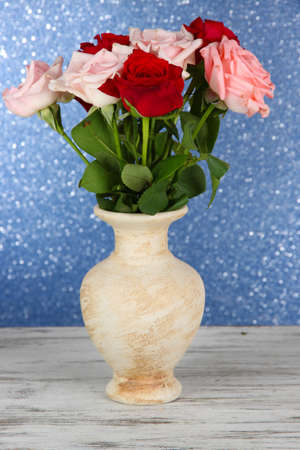 Beautiful bouquet of roses in vase on table on blue background photo