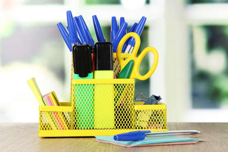 Office equipment in yellow stationary holder  on beige wooden table on window background