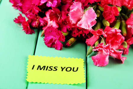 miss you: Bouquet of carnations, on color wooden background
