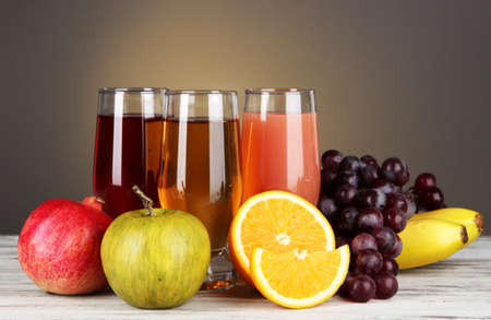 Glasses of fresh juice on table on gray background photo