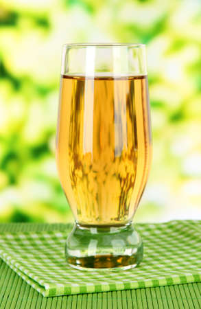 Glass of fresh apple juice on table on bright background photo