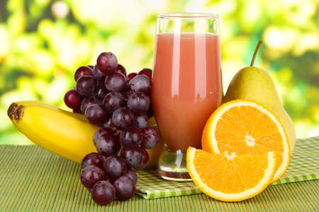 Glass of fresh juice on table on bright background photo