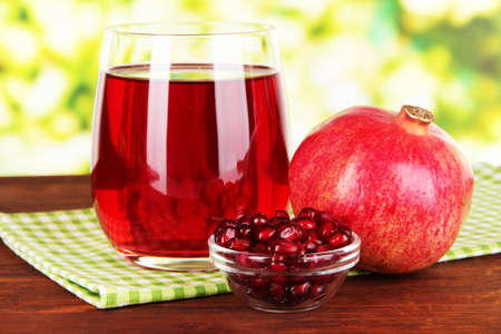 Glass of fresh garnet juice on table on bright background photo