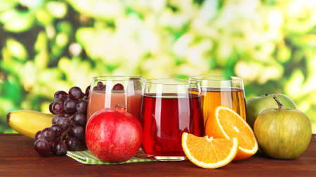 Glasses of fresh juice on table on bright background photo