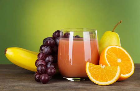 Glass of fresh juice on table on green background photo