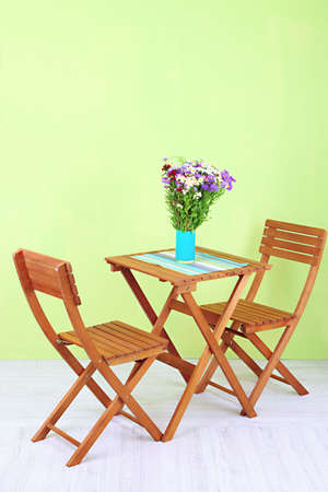 Wooden table with flower in room photo