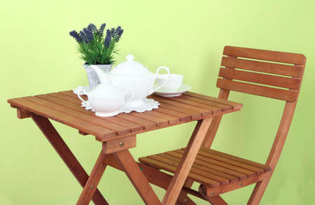 Wooden table with tea table setting on it on green background photo