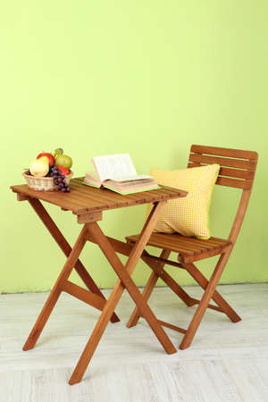 the green background: Wooden table with fruit and book on it in room