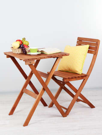 Wooden table with fruit,book and cup on it in room photo