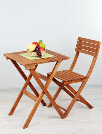 Wooden table with fruit in room photo