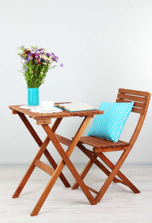 Wooden table with flower,book and cup on it in room photo
